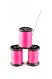 Spool of pink thread and needle Royalty Free Stock Images