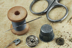 Thread with a needle, thimble, scissors and buttons Royalty Free Stock Photos
