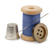 Thread, needle  and thimble. Spool of blue thread, needle, button  and thimble isolated on white Royalty Free Stock Photography