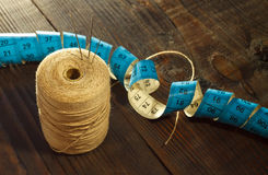 Thread, needles and  measuring meter. On wooden table Stock Photography