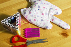 Thread, needles, scissors and a toy on the table. Royalty Free Stock Photo