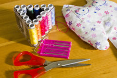Thread, needles, scissors and a toy on the table. Royalty Free Stock Photos