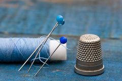 Thread, needles and thimble. Needle, thread and sewing thimble on a blue background Stock Photo