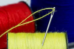 Thread roller and Sewing Needles. Close up Thread roller Blue, Red, Yellow and Sewing Needles in white background.Use to repair the tear of clothing royalty free stock photo