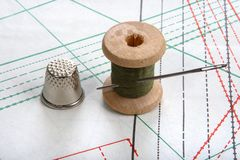 Thread on sewing plan. Thread with needle and thimble on sewing plan Stock Image