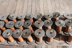 Thread and silk spools sit empty on a wooden floor  of an old ab Royalty Free Stock Photo