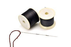 Thread spindles and needle Royalty Free Stock Photo