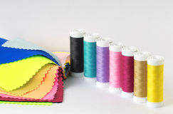 Thread spools. Spoos with different coloured threads and sample fabrics Stock Photo