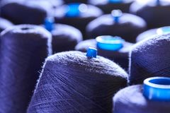 Thread in a textile factory. Purple thread with shallow depth of field on a shelf in a textile factory stock photos