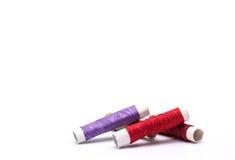 Thread tube Dark red, red, green, purple on white background Stock Photos