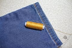 Thread of warm colors, jeans, sewing machine Royalty Free Stock Photography