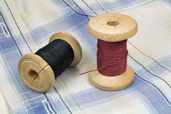 Thread on the wooden spools on a fabric background Stock Photography
