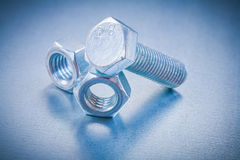 Threaded bolt detail and nuts on metallic Royalty Free Stock Photography