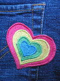 Threaded heart on  jeans. Stitched colorful heart on jeans Royalty Free Stock Photography