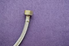 Threaded tap, reinforced, silver hose on a purple background. royalty free stock photo