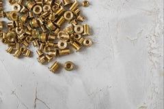 Threaded wszywka uzupełniająca od złocistego colour metalu na popielatym cementowym tle zbliżenie fotografia royalty free