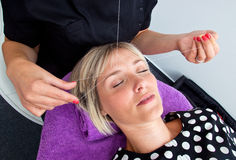 Threading hair removal. Beautician makes threading hair removal procedure to blond woman in salon Royalty Free Stock Photo