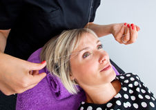 Threading hair removal. Beautician makes threading hair removal procedure to blond woman in salon Stock Images