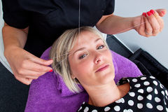 Threading hair removal. Beautician makes threading hair removal procedure to blond woman in salon Stock Photos