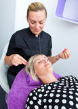 Threading hair removal. Beautician makes threading hair removal procedure to blond women in salon Royalty Free Stock Photo