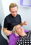 Threading hair removal. Beautician makes threading hair removal procedure to blond women in salon Royalty Free Stock Images