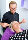 Threading hair removal. Beautician makes threading hair removal procedure to blond women in salon Stock Images