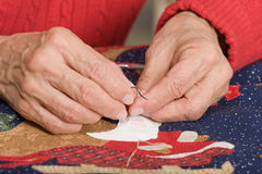 Threading the needle. A quilter puts black embroidery floss into the eye of the needle to begin stitching a Christmas quilt Stock Image