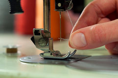 Threading the needle in a sewing machine. Royalty Free Stock Images