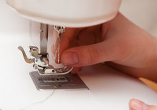 Threading a thread in a sewing machine Royalty Free Stock Image