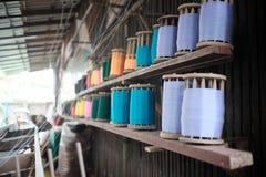 Threadreihe auf hölzerner Latte Stockfoto