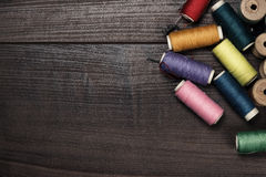 Threads on brown wooden table background Stock Image