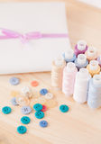 Threads, buttons, fabric on wooden table Royalty Free Stock Photo