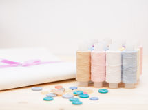 Threads, buttons, fabric on wooden table Royalty Free Stock Images