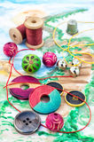Threads and embellishments on a colorful background. Accessories of beads and threads for needlework on wooden plank Stock Images