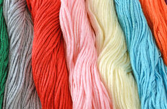 Threads for embroidery. Colored threads for embroidery cross on canvas Royalty Free Stock Images