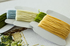 Threads for embroidery in natural colors. Paper bobbins with thread for embroidery and a fragment of embroidery on the background of the canvas. Selective focus Royalty Free Stock Images