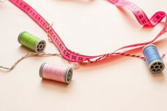 Sewing centimeter pink color and thread on a beige background. stock photo