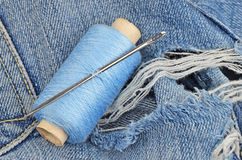 Threads on jeans, wear repair concept. Threads and needle on jeans backround, wear repair concept Royalty Free Stock Image