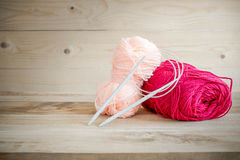 Threads for knitting with spokes on wooden table Royalty Free Stock Photo