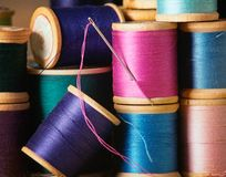 Threads with Needle. Spools of colorful old thread stacked in pile Royalty Free Stock Photo
