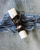 Threads and needle on jeans backround Royalty Free Stock Photo