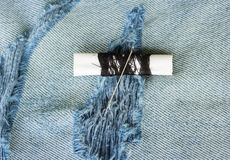 Threads and needle on jeans backround Stock Photo