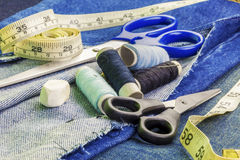 Threads with needles, scissors, and tape measure on denim fabric Stock Photos