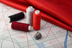 Threads and  red fabric on lie to the pattern. Threads, red fabric and thimble on lie to the pattern Stock Images