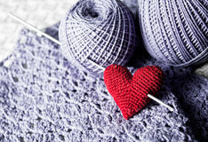 Threads with red handmade knitted  heart Stock Image