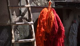 The threads of red and orange colored fabrics hung to dry near the stairs. The perfumes of the colors and craftsmanship of the markets of the eastern cities Stock Image