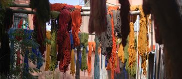The threads of red and orange colored fabrics hung to dry near the stairs. The perfumes of the colors and craftsmanship of the markets of the eastern cities Royalty Free Stock Photo