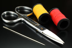 Threads, scissors and needle on a black background Royalty Free Stock Image