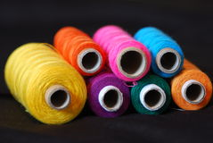 Threads for sewing. Colorful threads for sewing on the black background Royalty Free Stock Images
