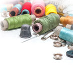 Threads_and_sewing_supplies_background. Colorful threads on white painted wooden background with space for your text Royalty Free Stock Images